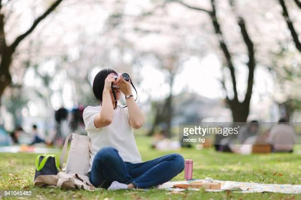 ピクニック中に写真を撮る若い女性