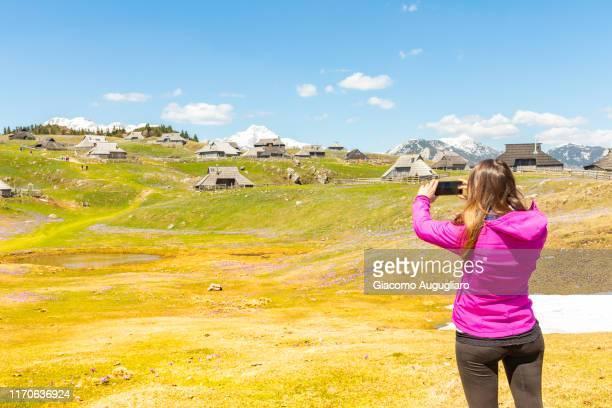 young woman taking photos of an old shepherd village at velika planina in the background, stahovica, upper carniola region, slovenia, europe - eden pastora fotografías e imágenes de stock