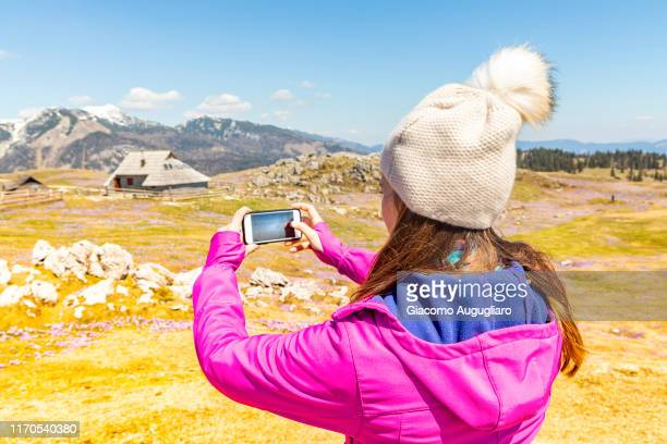 young woman taking photos of an old shepherd village at velika planina during crocus flowering, stahovica, upper carniola region, slovenia, europe - eden pastora fotografías e imágenes de stock