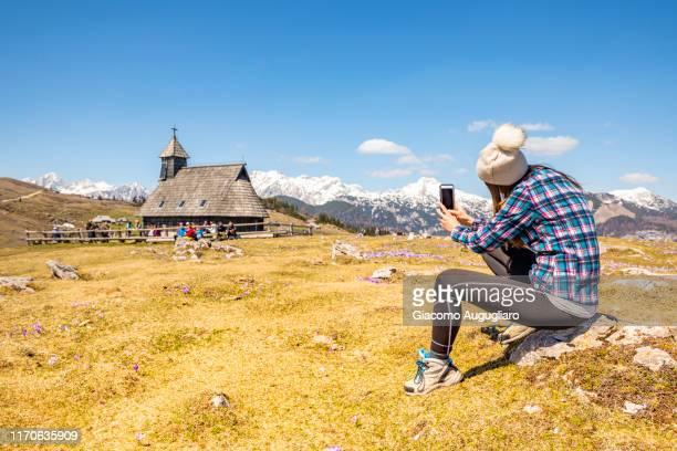 young woman taking photos of the wooden church of our lady of the snows at velika planina, stahovica, upper carniola region, slovenia, europe - eden pastora fotografías e imágenes de stock