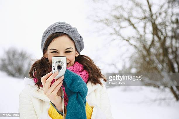 Young woman taking picture in snow