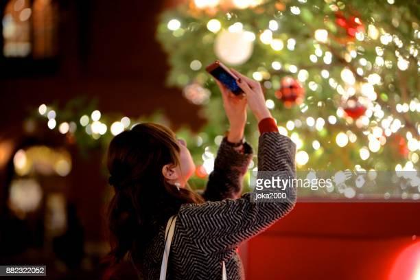 若い女性は、クリスマス ツリーの写真を撮る