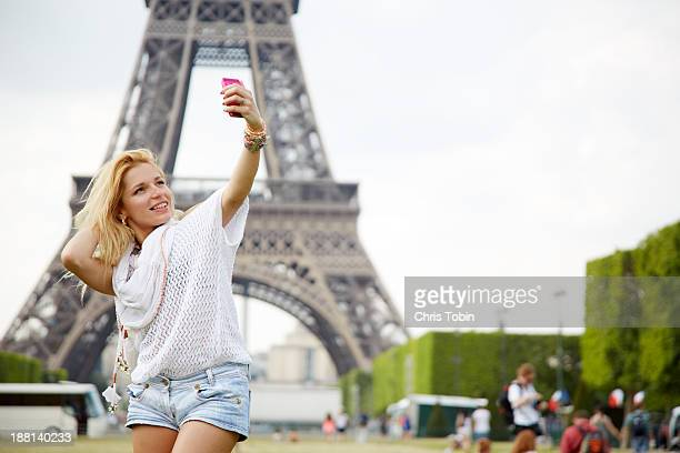 Young woman taking picture of herself Eiffel Tower
