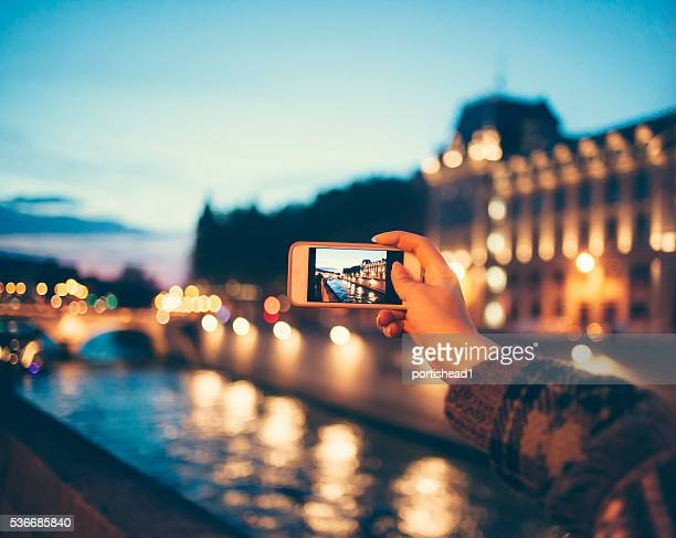 young woman taking picture of river bridge by night - photo messaging stock photos and pictures
