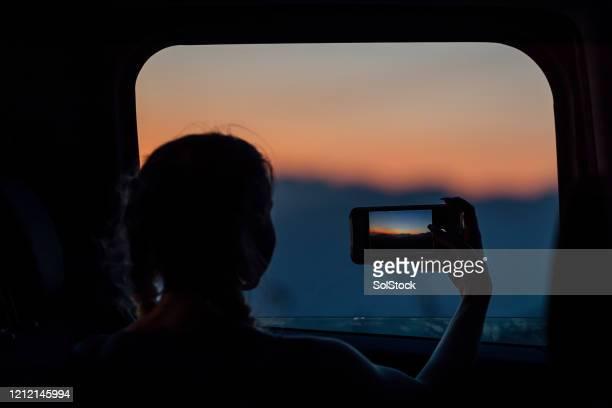 young woman taking picture of sunset from mini van - mensagem com foto imagens e fotografias de stock