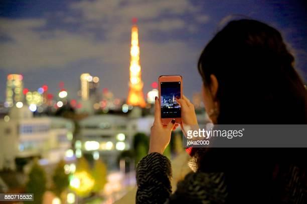 若い女性は、東京タワーの写真を撮る
