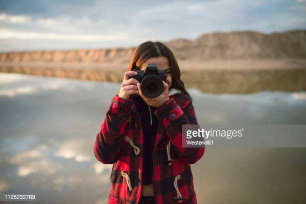 young woman taking picture with camera on the beach - fotógrafo fotografías e imágenes de stock