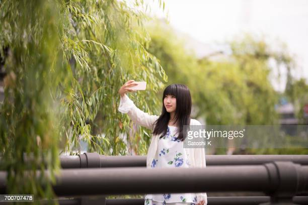 Young woman taking picture with smart phone