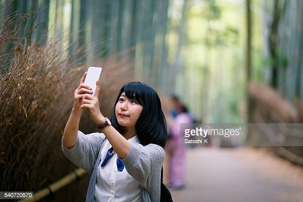 Young woman taking pictures in bamboo forest, Kyoto