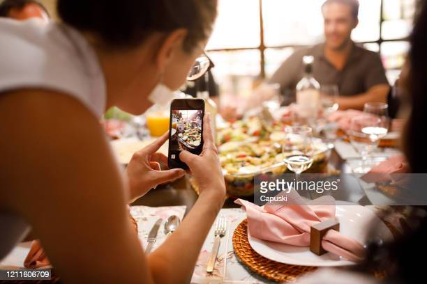 young woman taking pictures of food - easter dinner stock pictures, royalty-free photos & images