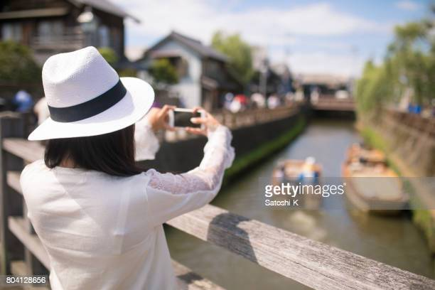 young woman taking pictures of old japanese town - capturing an image stock pictures, royalty-free photos & images
