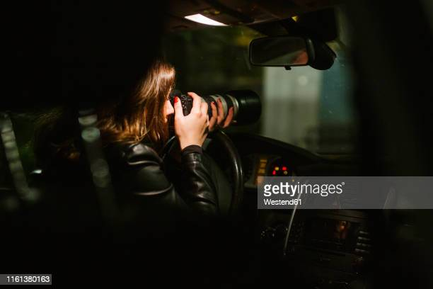 young woman taking pictures with a camera out of a car at night - photographe professionnel photos et images de collection