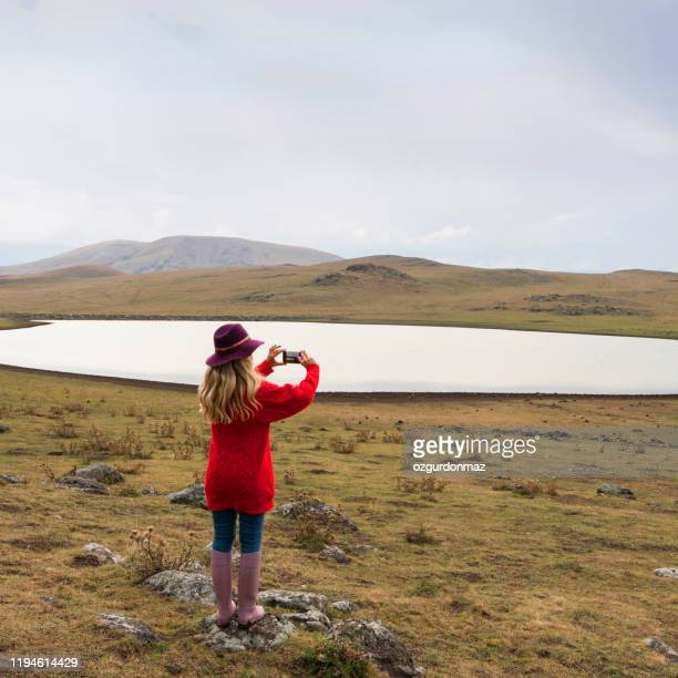 young woman taking pictures with phone near the lake - wilderness stock pictures, royalty-free photos & images
