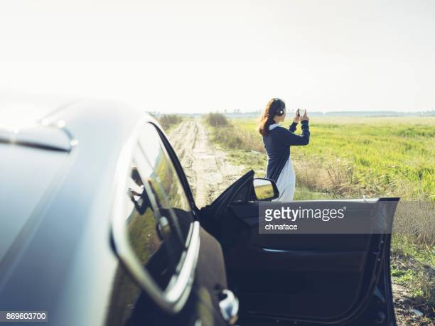 young woman taking pictures with smartphone against modern automobile