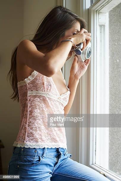 young woman taking polaroid shot out of window - vouyer fotografías e imágenes de stock