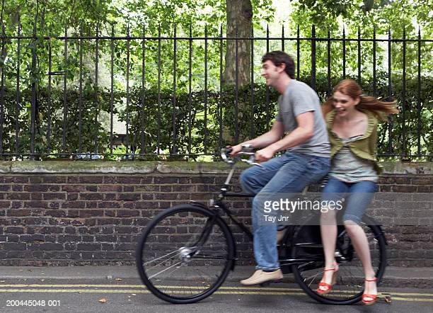 Young woman taking ride on back of man's bike (blurred motion)