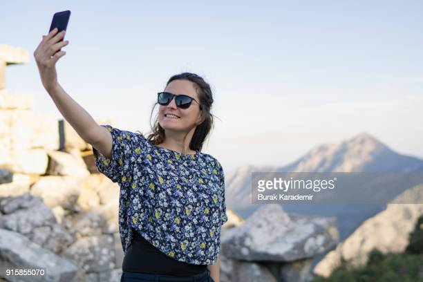 Young woman taking self portrait in mountain