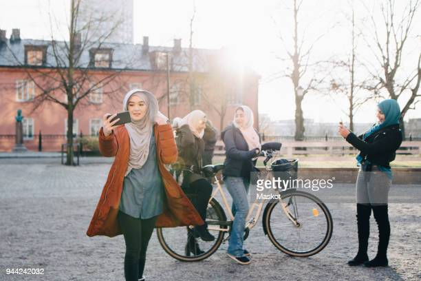 Young woman taking selfie against female friends with bicycle in city