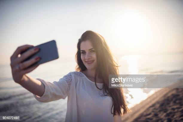 Jeune femme prenant selfie sur la plage