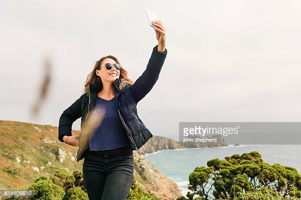 Young Woman taking Selfie at the Cornish Coast.