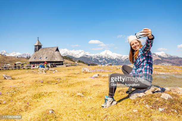 young woman taking selfie at the wooden church of our lady of the snows in velika planina, stahovica, upper carniola region, slovenia, europe - eden pastora fotografías e imágenes de stock