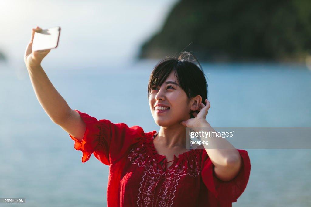 Junge Frau, die die Selfie am Meer : Stock-Foto