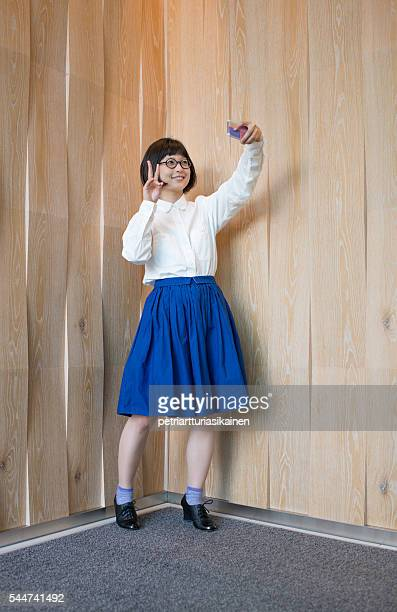 Young woman taking selfie by wooden wall.