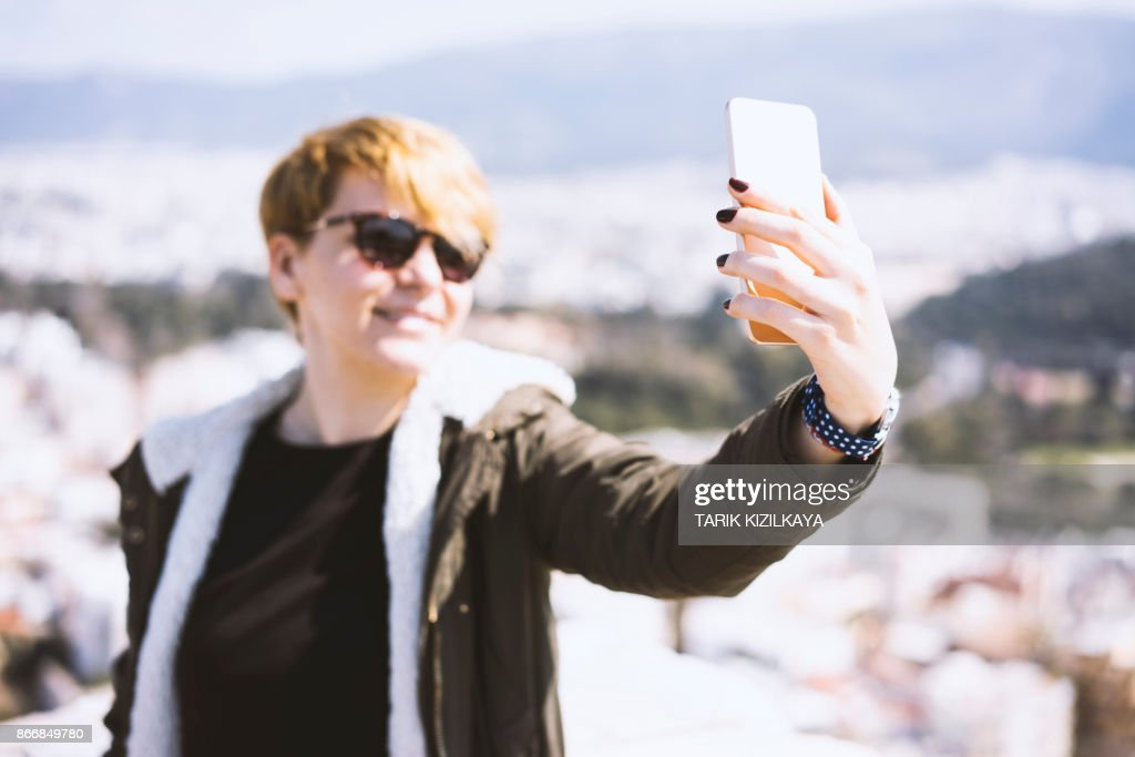 Young Woman Taking Selfie Outdoors With Mask On High-Res