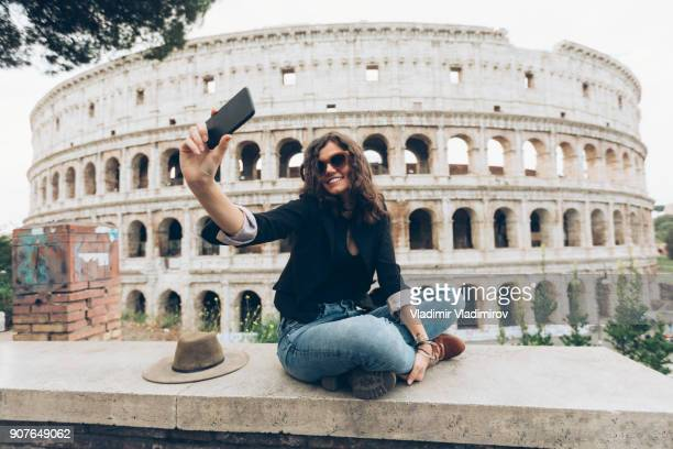 young woman taking selfie in front of coliseum - coliseum rome stock photos and pictures