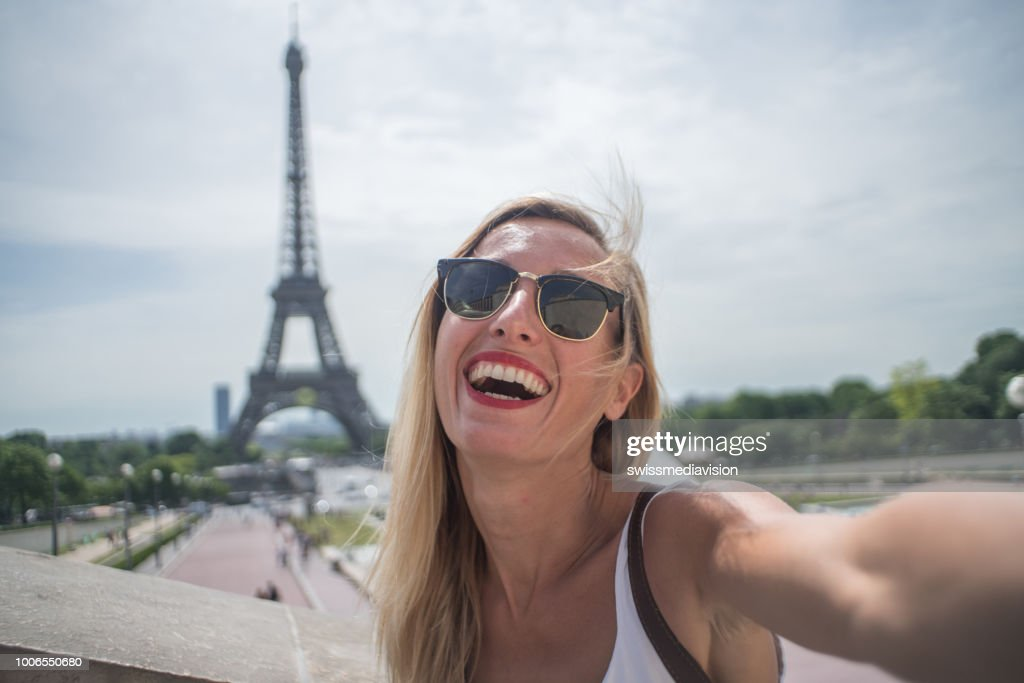 Young woman taking selfie in Paris city using mobile phone : Stock Photo