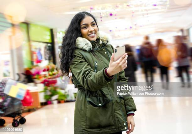 young woman taking selfie in shopping mall - 毛皮の飾り ストックフォトと画像