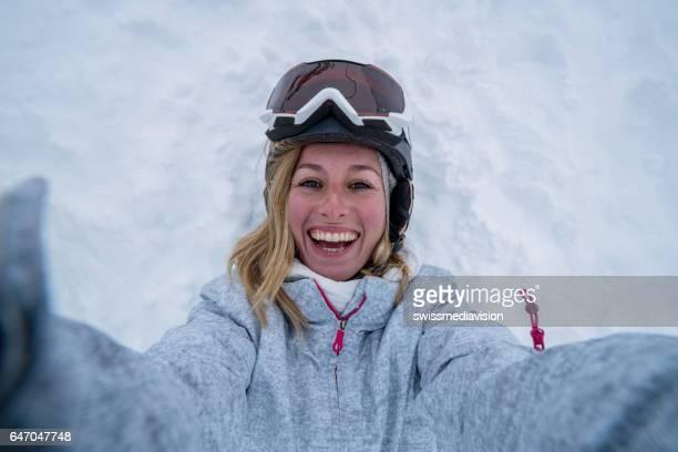 junge frau, die die selfie liegend auf schnee - lying down stock-fotos und bilder