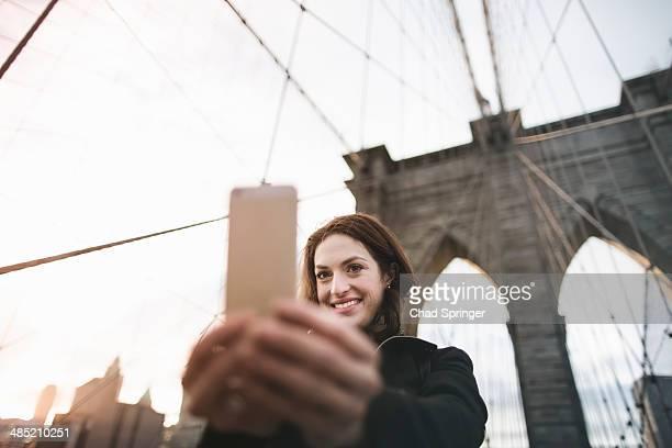 Young woman taking selfie on Brooklyn bridge, New York, USA