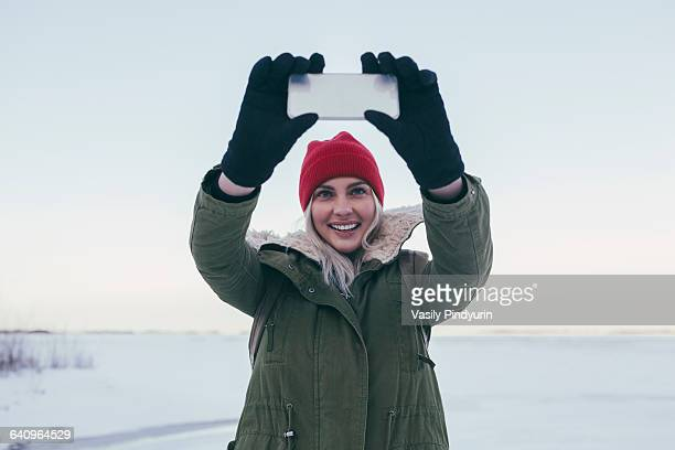 Young woman taking selfie on smart phone during winter