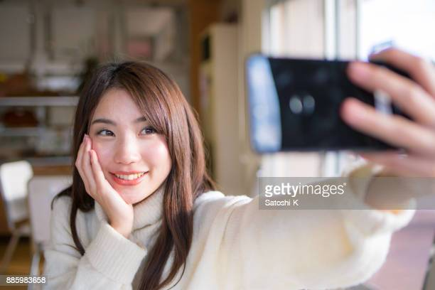 young woman taking selfie picture in cafe - self portrait stock pictures, royalty-free photos & images