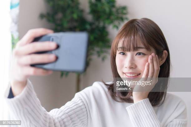 young woman taking selfie picture in living room - self portrait photography stock pictures, royalty-free photos & images