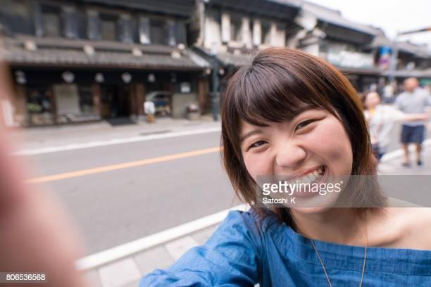 伝統的な日本の町で selfie 写真を撮る若い女性