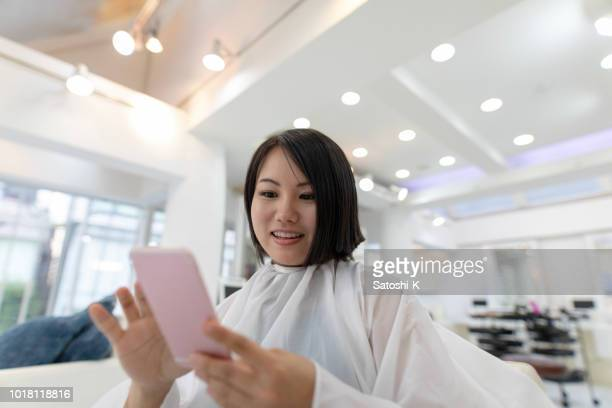 Young woman taking selfie picture just after 30cm haircut