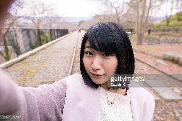 Young woman taking selfie picture on dead railroad track