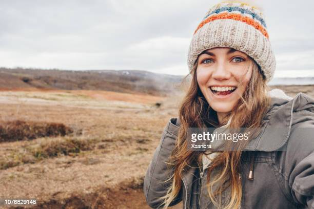 young woman taking selfie portrait in iceland - parka coat stock photos and pictures