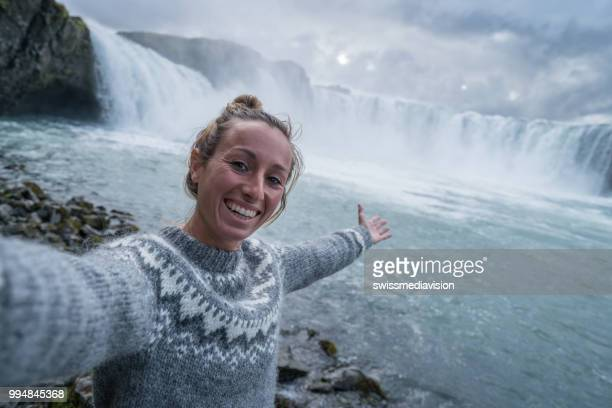 Young woman taking selfie portrait with magnificent waterfall in Iceland, Godafoss falls. People travel exploration concept