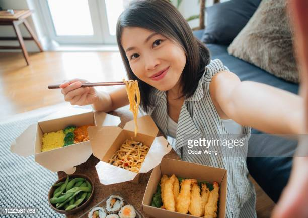 young woman taking selfie while eating takeaway food - lunch stock pictures, royalty-free photos & images