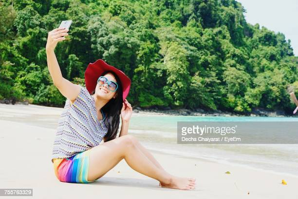 young woman taking selfie while sitting at beach - mid adult stock pictures, royalty-free photos & images