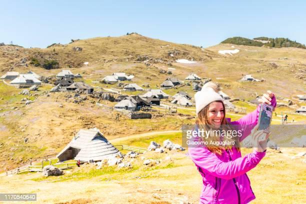 young woman taking selfie with an old shepherd village at velika planina in the background, stahovica, upper carniola region, slovenia, europe - eden pastora fotografías e imágenes de stock