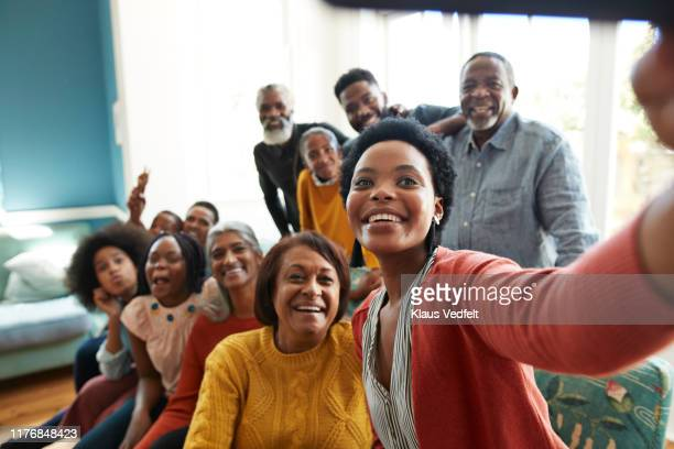 young woman taking selfie with family and friends - photo messaging stock pictures, royalty-free photos & images