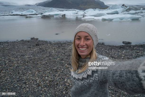 Young woman taking selfie with glacier lake, icebergs floating on water