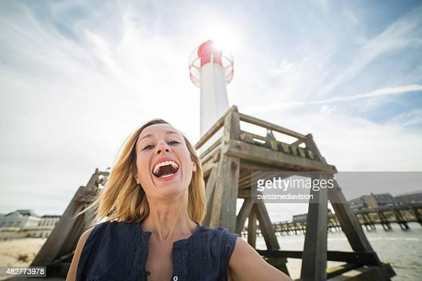 Jeune femme prenant selfie avec phare de Normandie