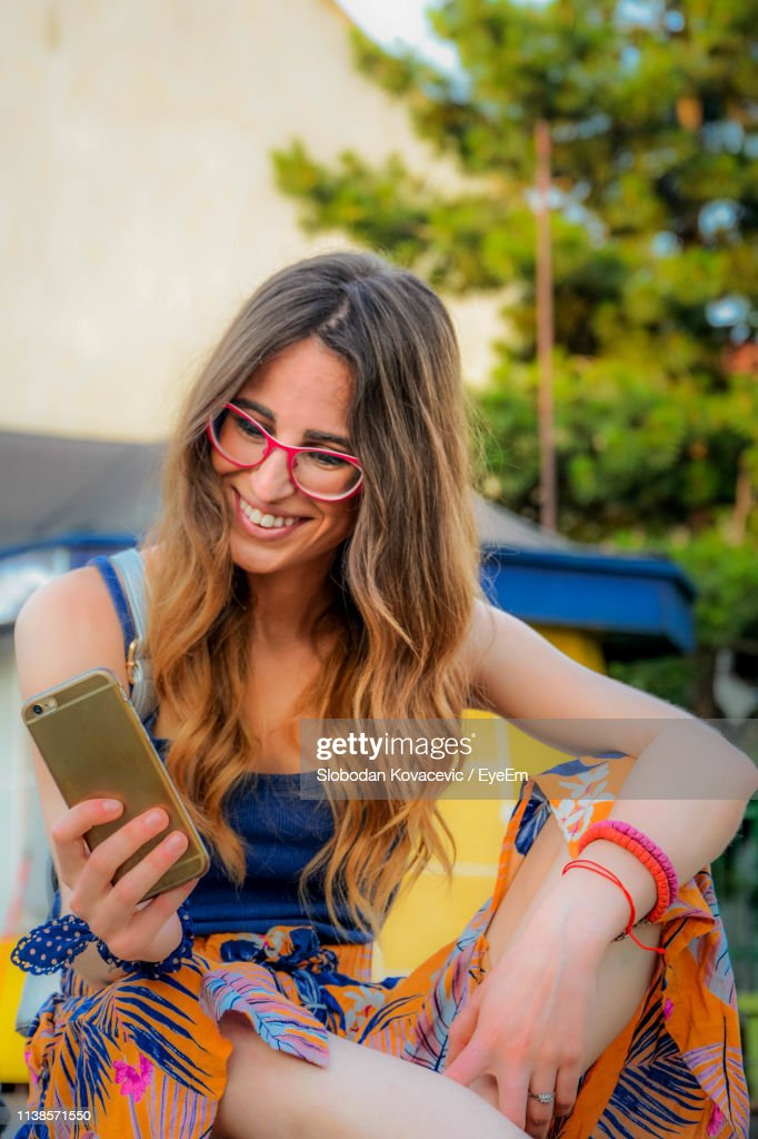 Young Woman Taking Selfie While Sitting At Restaurant High
