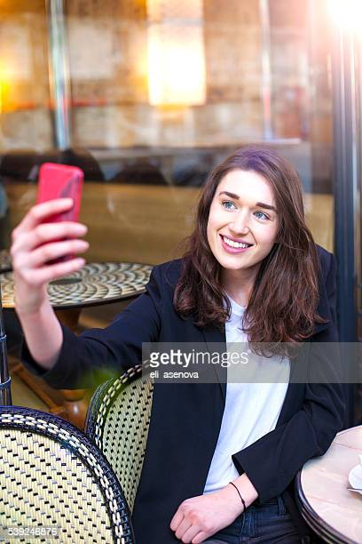 Young woman taking selfie with smart phone in cafe Paris