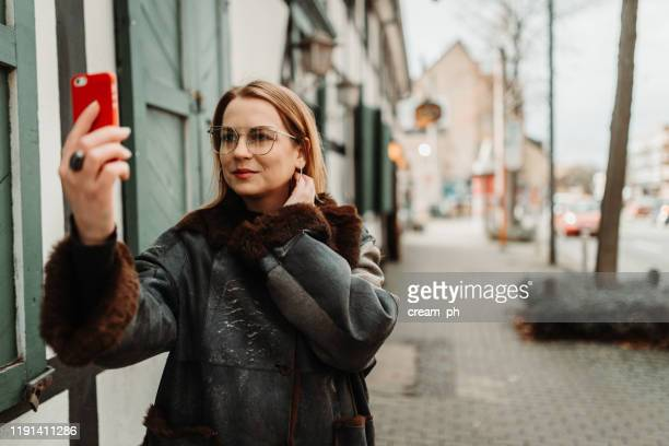 young woman taking selfie with smart phone in the city street - dortmund stock pictures, royalty-free photos & images